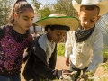 Sarela Gabaldón, left, Sophie Roth-Gordon, center, and Alek Figueroa, right, observe plants inside Davis Bilingual Magnet School's garden in Tucson, Ariz. on Wednesday, Feb. 25, 2015. The first graders later will write down what they observed in their journals. Photographed by Noelle Haro-Gomez