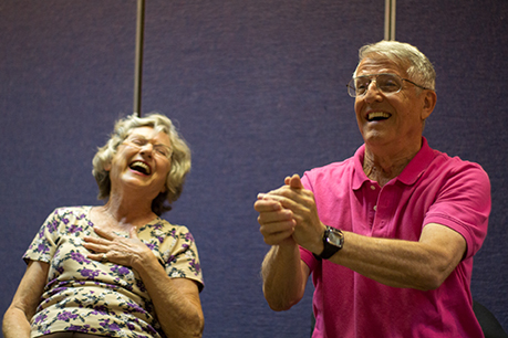 Gail Lawley, left, laughs with Hank Mosser, right, during Laughter Yoga in Tucson, Ariz. on Tuesday, Feb. 3, 2015. Mosser is trapping an imaginary ball in his hands during a laughter excercise. Photographed by Noelle Haro-Gomez