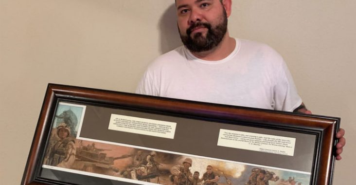 Beto Ureña depicted here 16 years after the invasion of Baghdad holding a plaque remake of the famous photograph of him during the war that was given to him by his unit, 3/7, after the end of his enlistment in the Marines. (Photo by Alberto Quiroz).