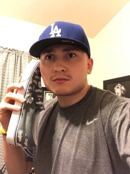 Adriell Alvarado jokingly holds one of his numerous pairs of sneakers (Photo by Ahmaad Lomax).