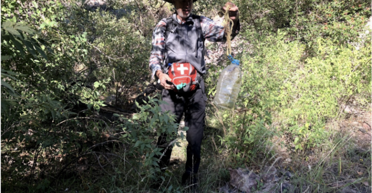 Brian Best, Tucson Samaritans member, recovers a water jug from the bushes in a canyon of Peña Blanca in Coronado National Forest. Photo: MacKenzie Carolan | El Inde.