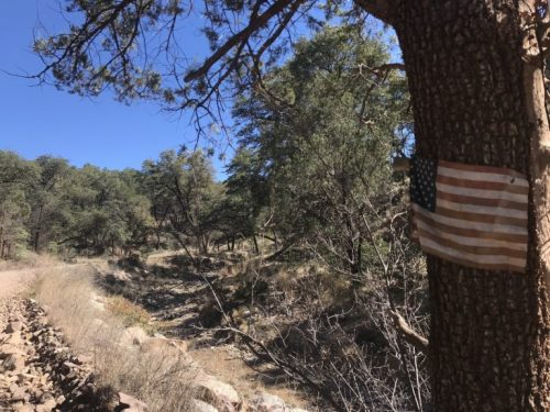 Along a dirt road through Harshaw, an American Flag is pinned on a tree. These roads are heavily trafficked by Sonoita Station Border Patrol agents. (Photo by Clara Migoya/El Inde).