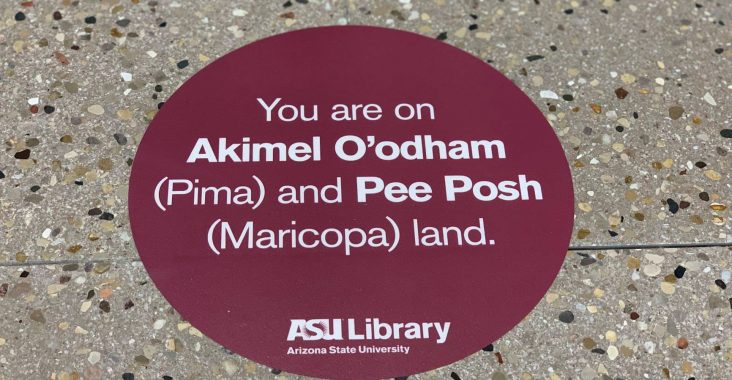 "A red sticker on the ASU Library floor reads, ""You are on Akimel O'odham (Pima) and Pee Posh (Maricopa) land."""